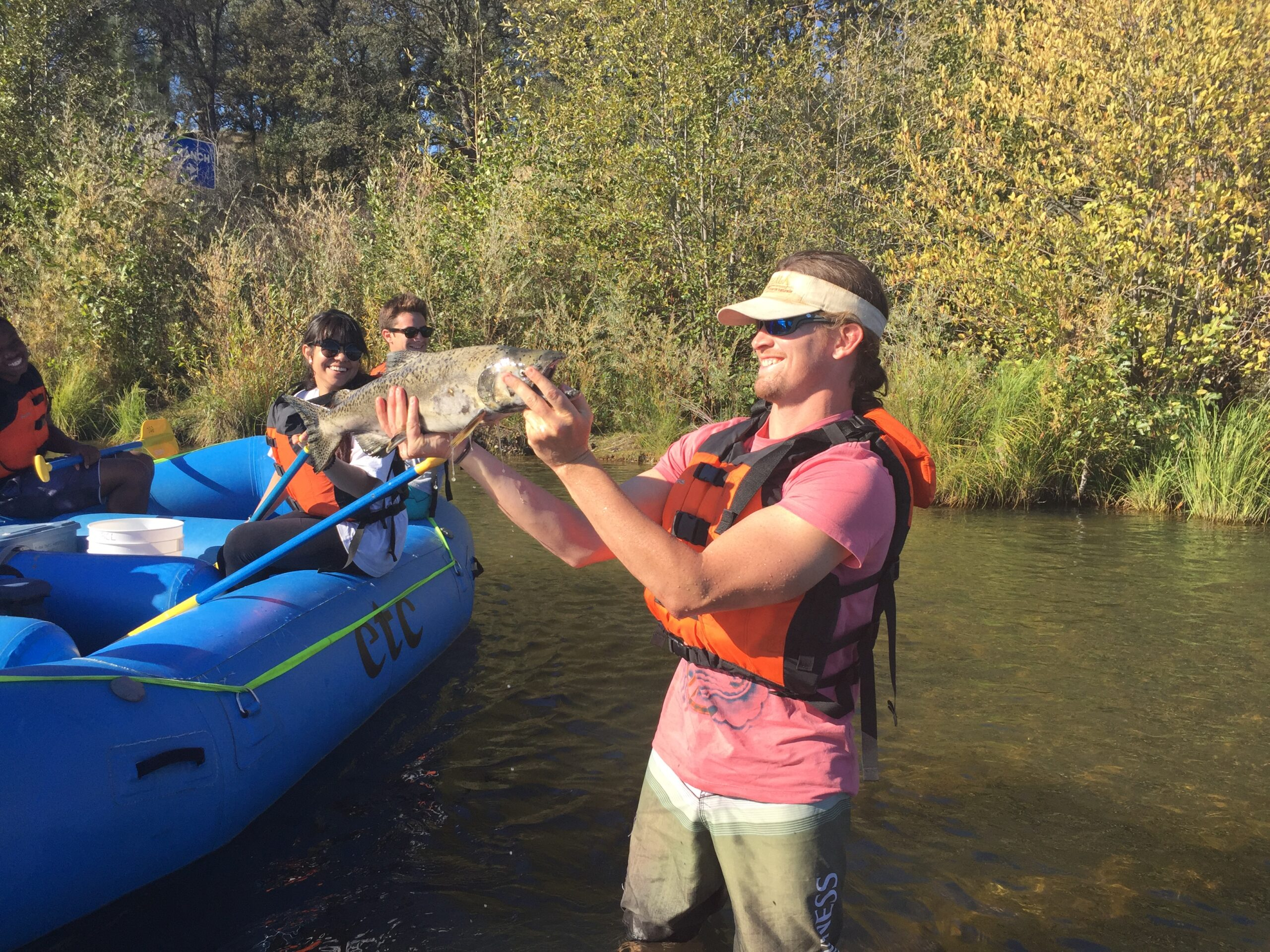 Man holding fish at river raft trip on the Yuba River