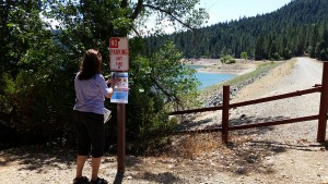 Volunteer posting state-issued fish consumption advisory sign at Scotts Flat Reservoir on July 11, 2015