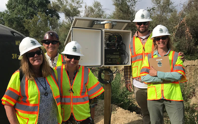 The Sierra Fund staff standing in front of real-time monitoring equipment at Combie Reservoir