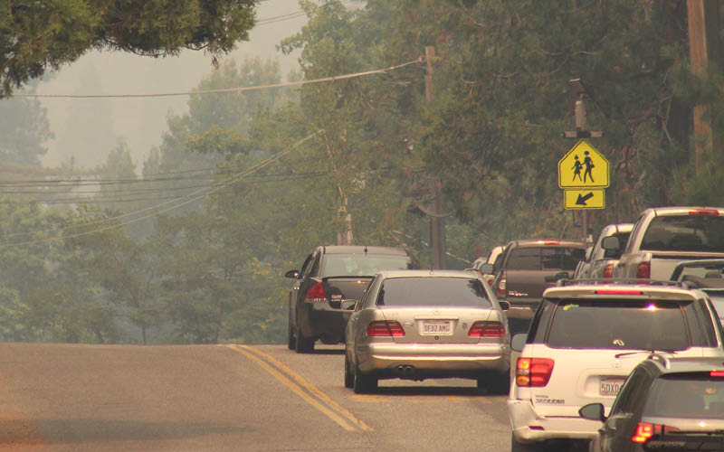 A line of cars evacuating in smoky conditions